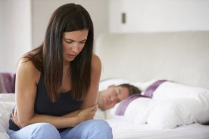 Woman Sitting On Bed And Feeling Unwell