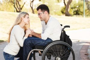 Young girl sitting in front of her boyfriend in a wheelchair in the park.